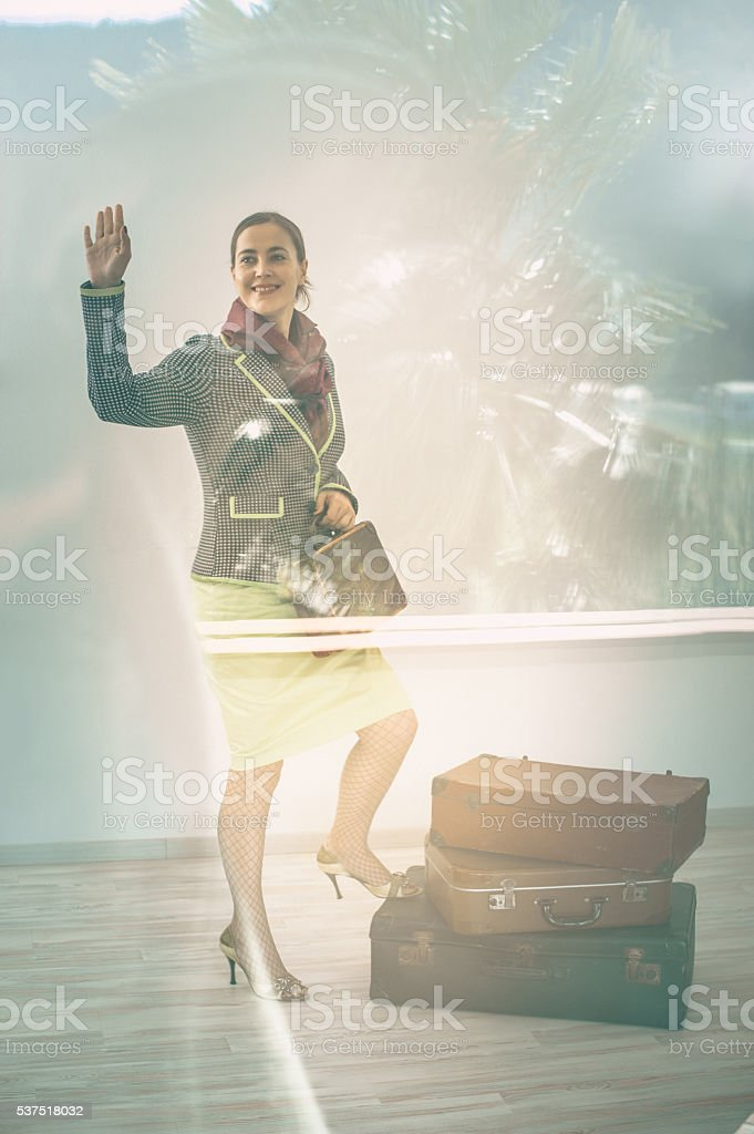 Woman with suitcases saying goodby stock photo