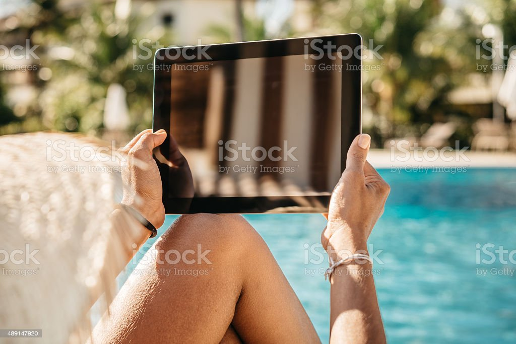 woman with sun hat holding digital tablet at swimming pool stock photo