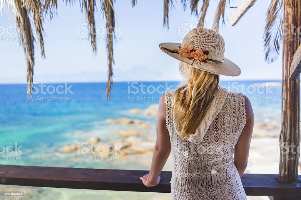 Woman with sun hat looking at beach from above. stock photo