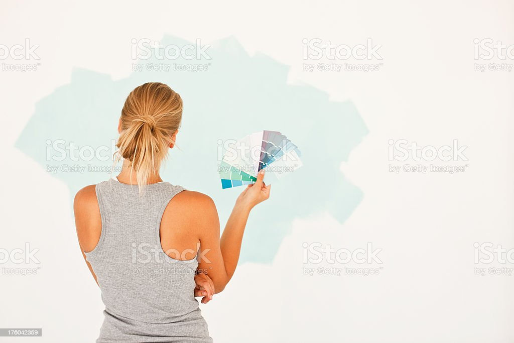 Woman with swatches standing in front of a painted wall royalty-free stock photo
