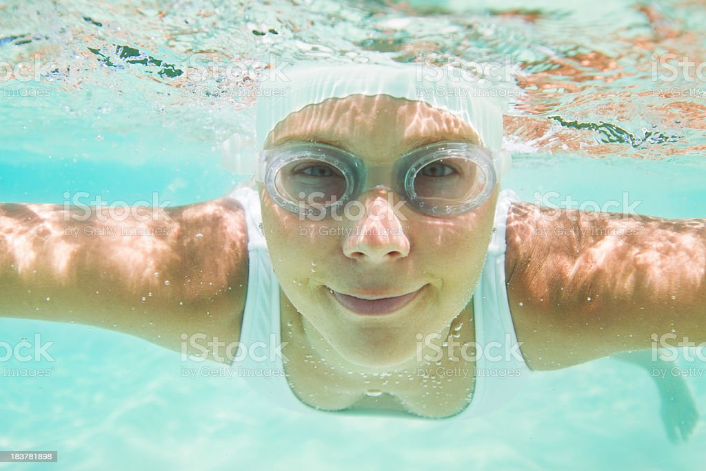 woman with swimming cap and goggles diving underwater royalty-free stock photo