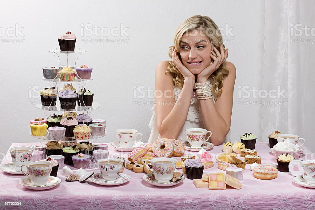 Woman with table of tea and cakes stock photo