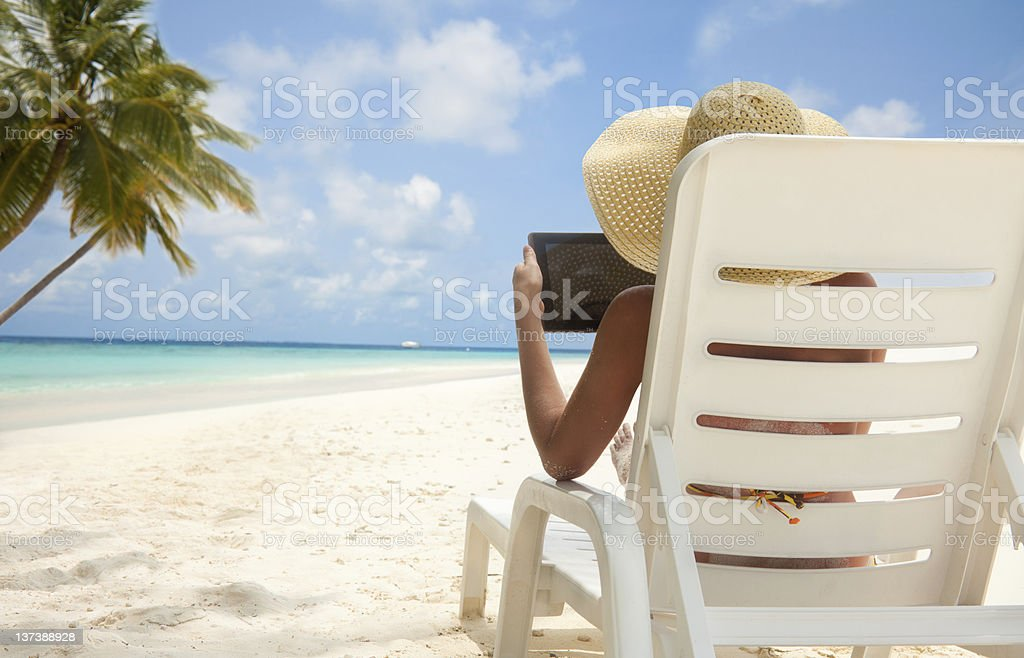 Woman with tablet computer on the beach royalty-free stock photo