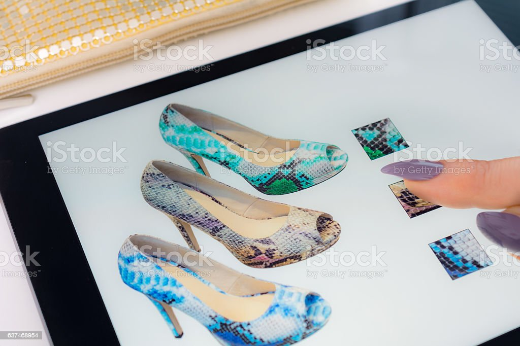 Woman with Tablet selecting snakeskin peeptoe pumps online stock photo