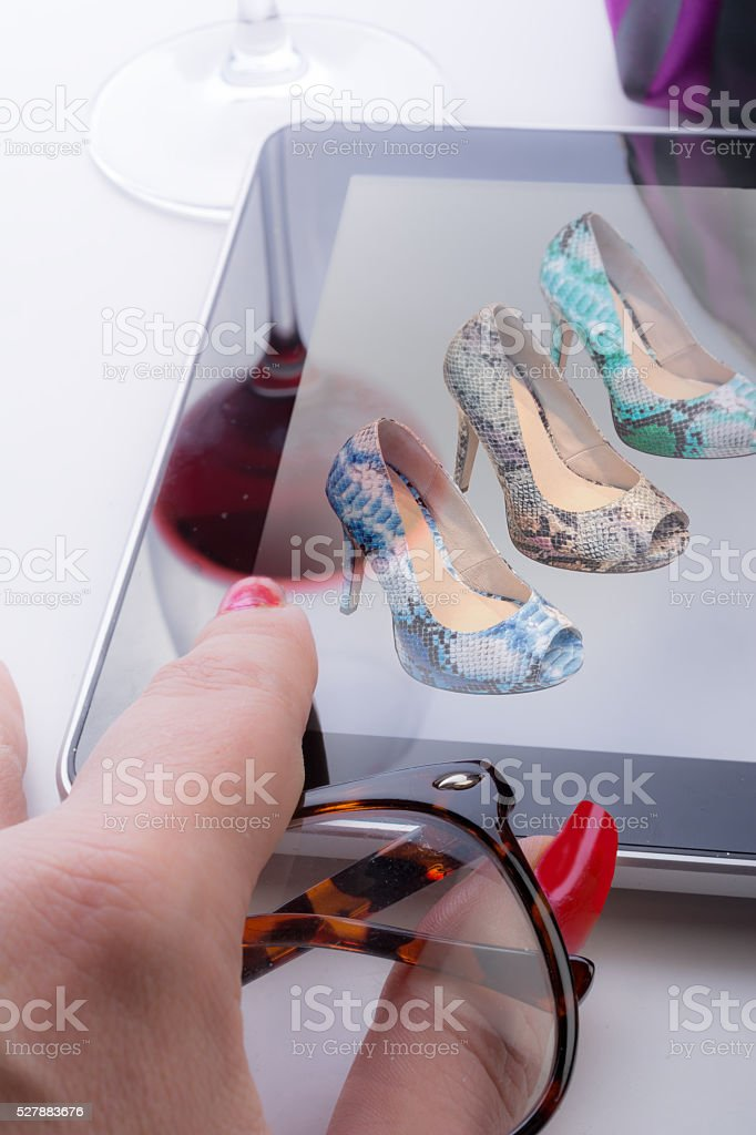 Woman with Tablet viewing snakeskin peeptoe pumps online stock photo