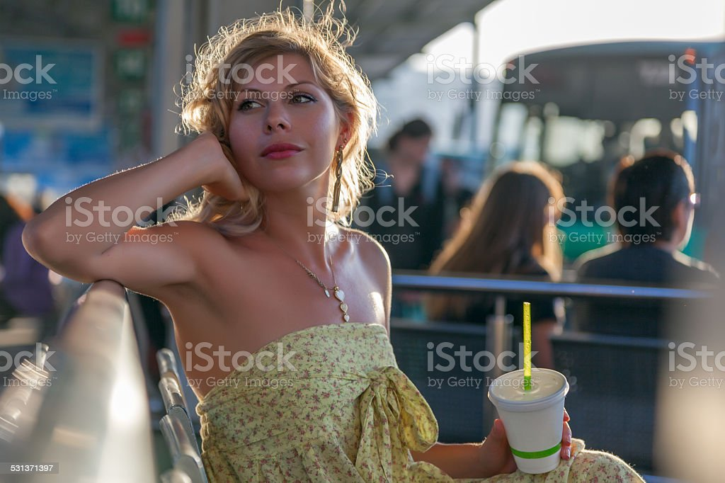 Woman with take out drink waiting at bus station stock photo