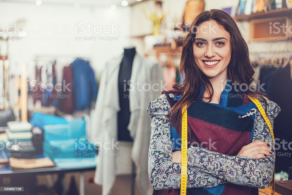 Woman with tape measure in fashion department stock photo