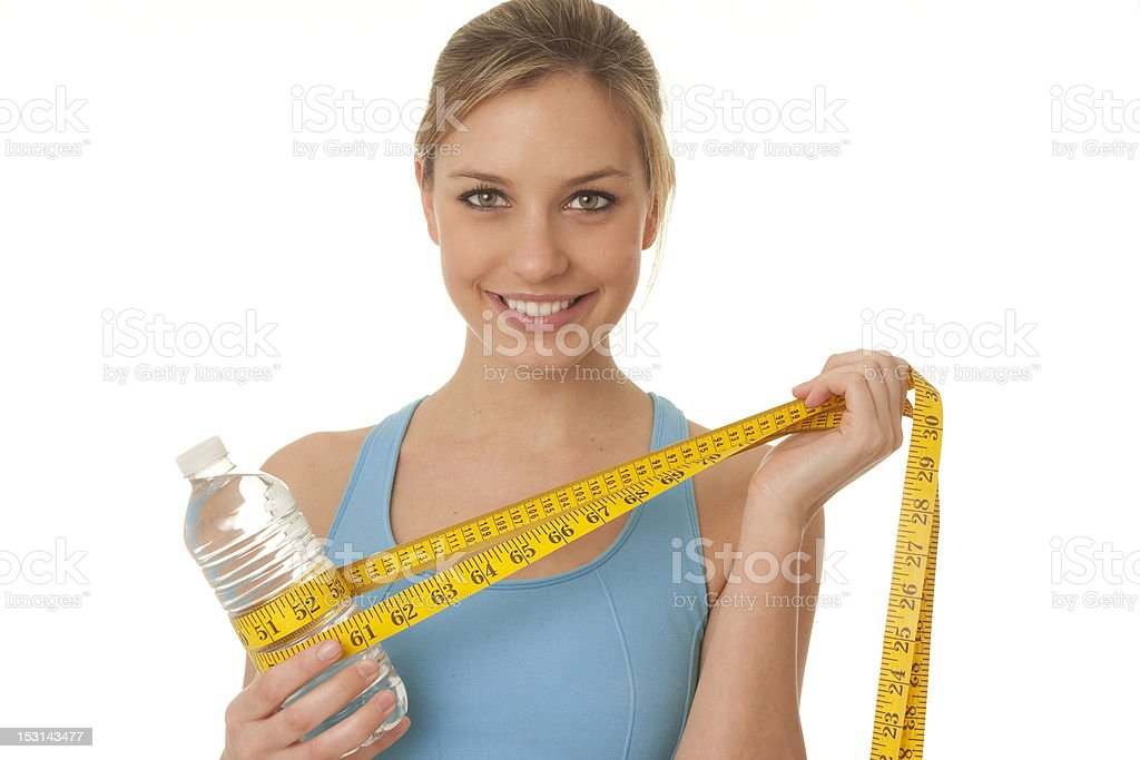 woman with tape measure wrapped around water bottle royalty-free stock photo