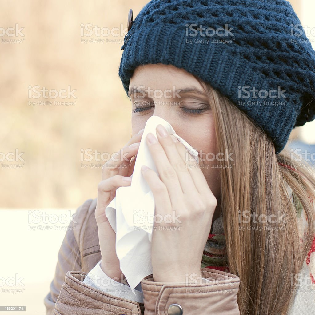 A woman with the flu blowing her nose royalty-free stock photo