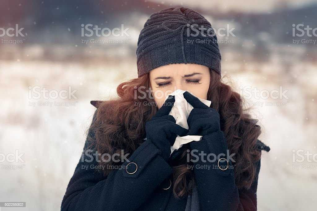 Woman with Tissue Outside Feeling Bad Cold Winter stock photo