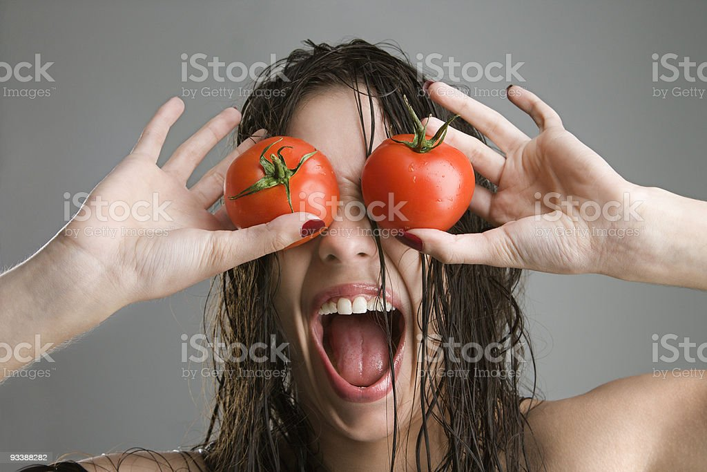 Woman with tomatoes covering eyes. royalty-free stock photo