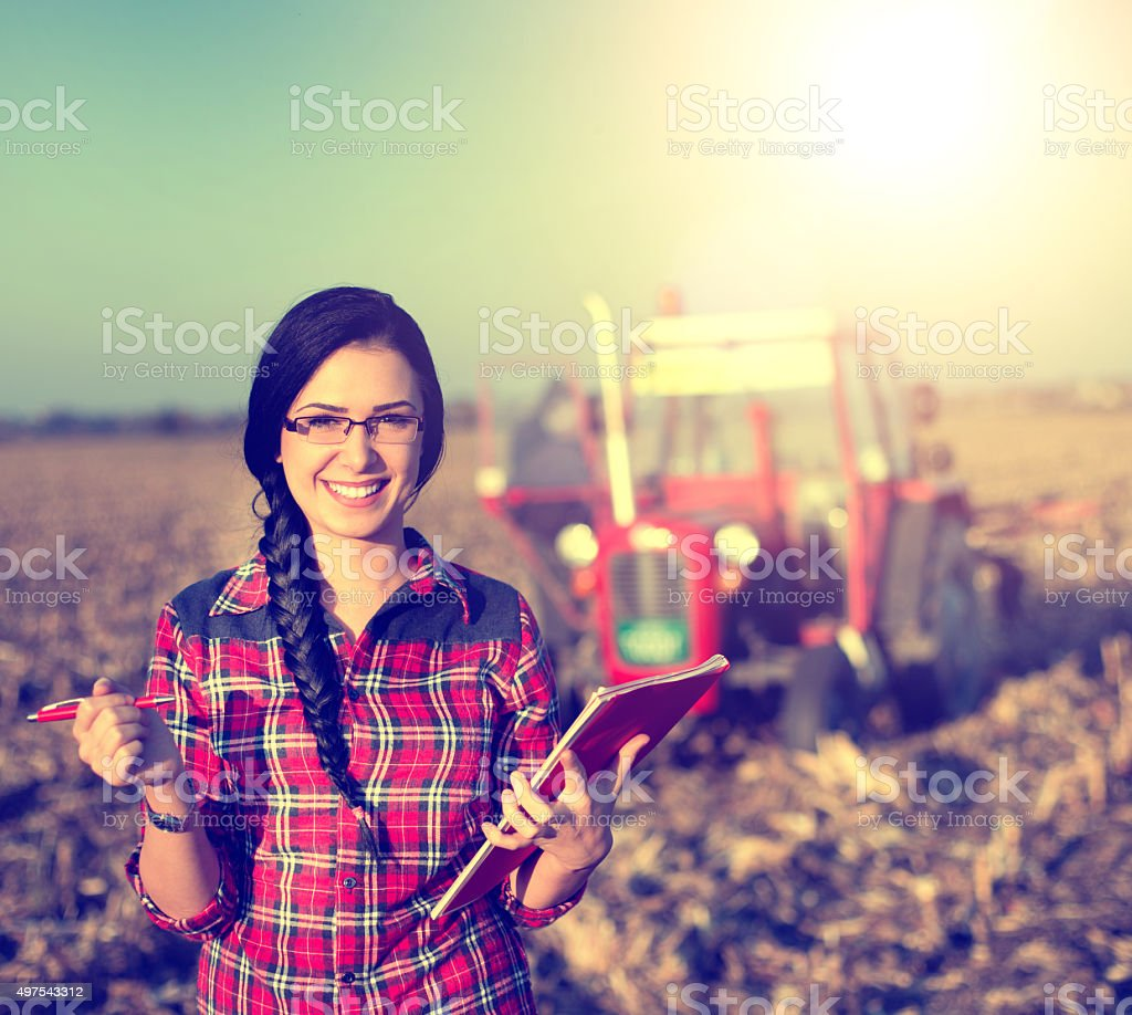 Woman with tractor on the field stock photo