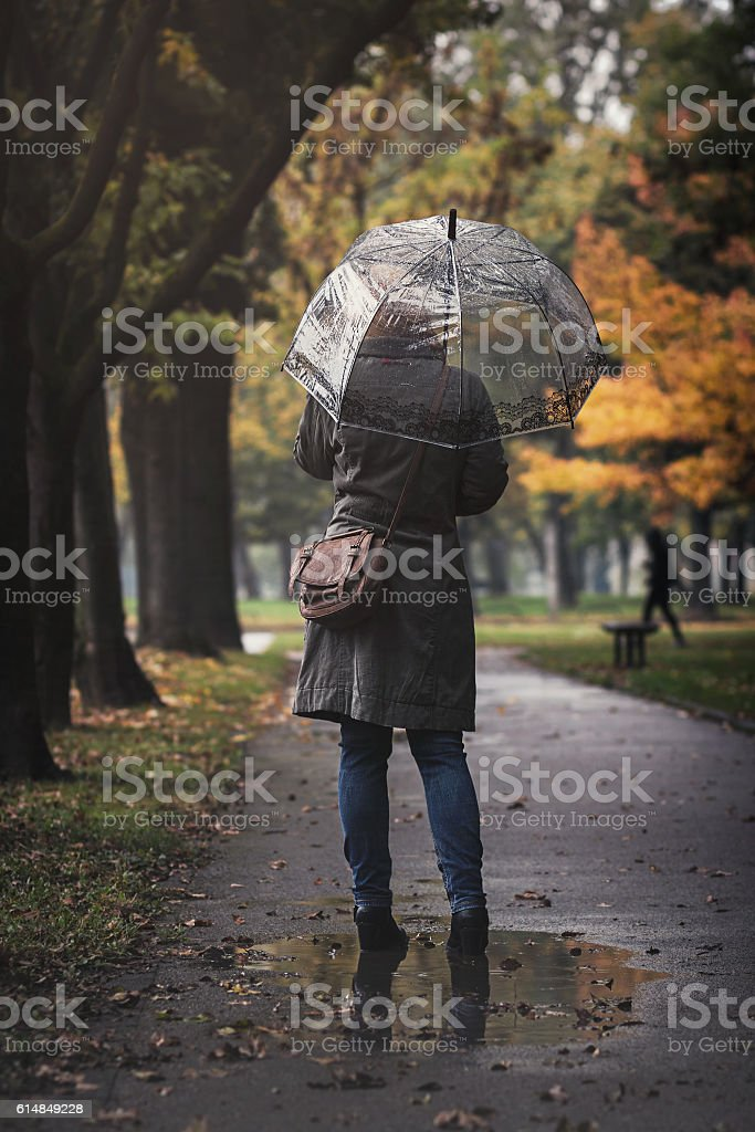 Woman with transparent umbrella on a rainy day stock photo