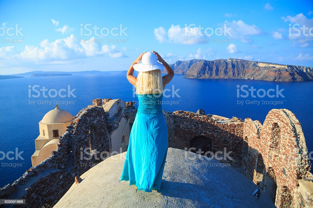 Woman with turquoise dress in Santorini, Greece. stock photo