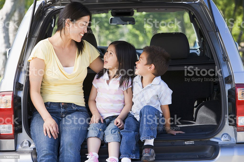 Woman with two children sitting in back of van smiling royalty-free stock photo