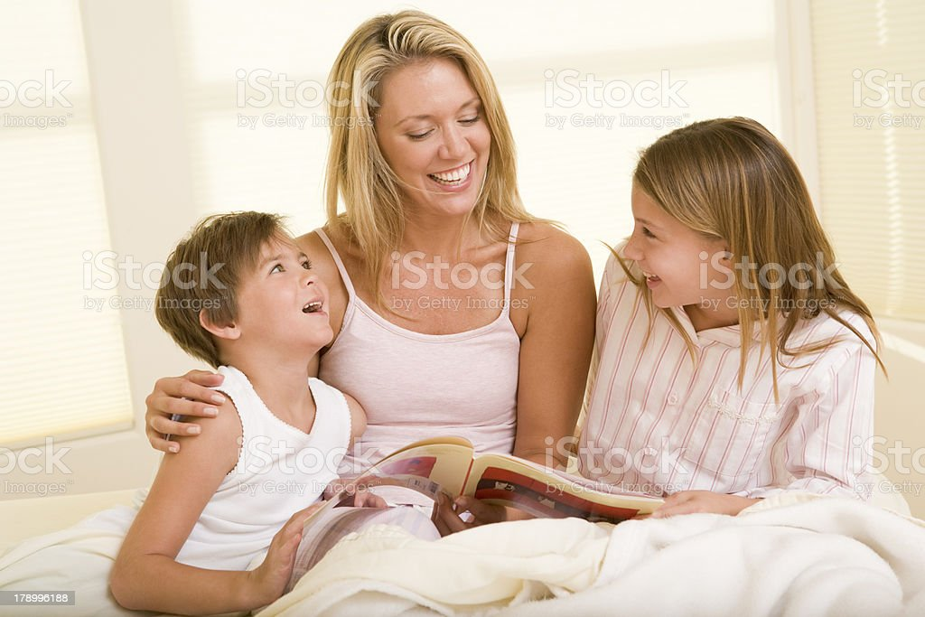 Woman with two young children sitting in bed reading book royalty-free stock photo