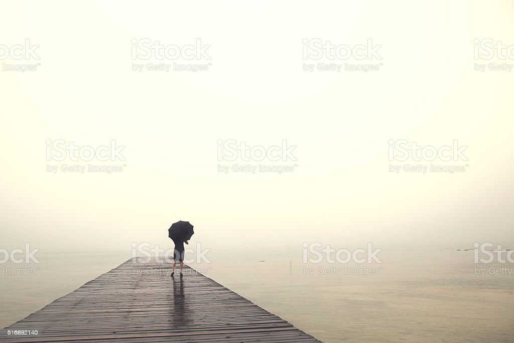 woman with umbrella contemplates peacefully in front of  lake stock photo