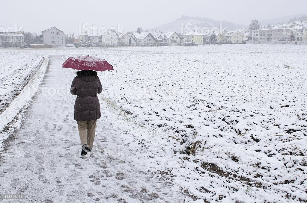 Woman with umbrella is strolling in the snow royalty-free stock photo