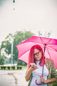 Woman with umbrella looking her cellphone in the street.