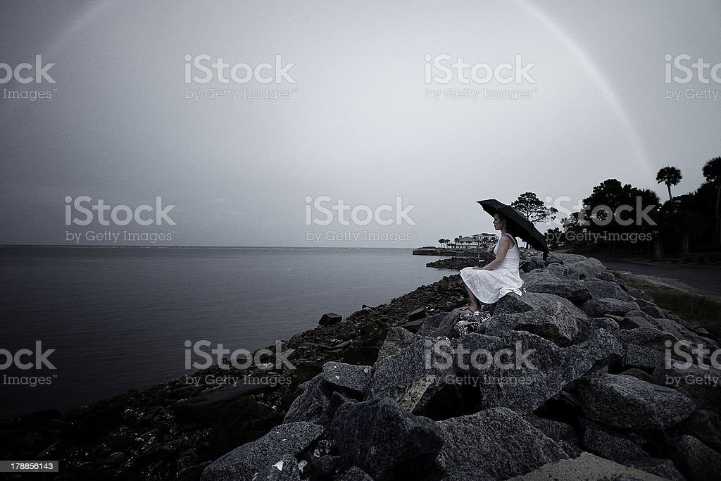 Woman with umbrella on beach and rainbow royalty-free stock photo