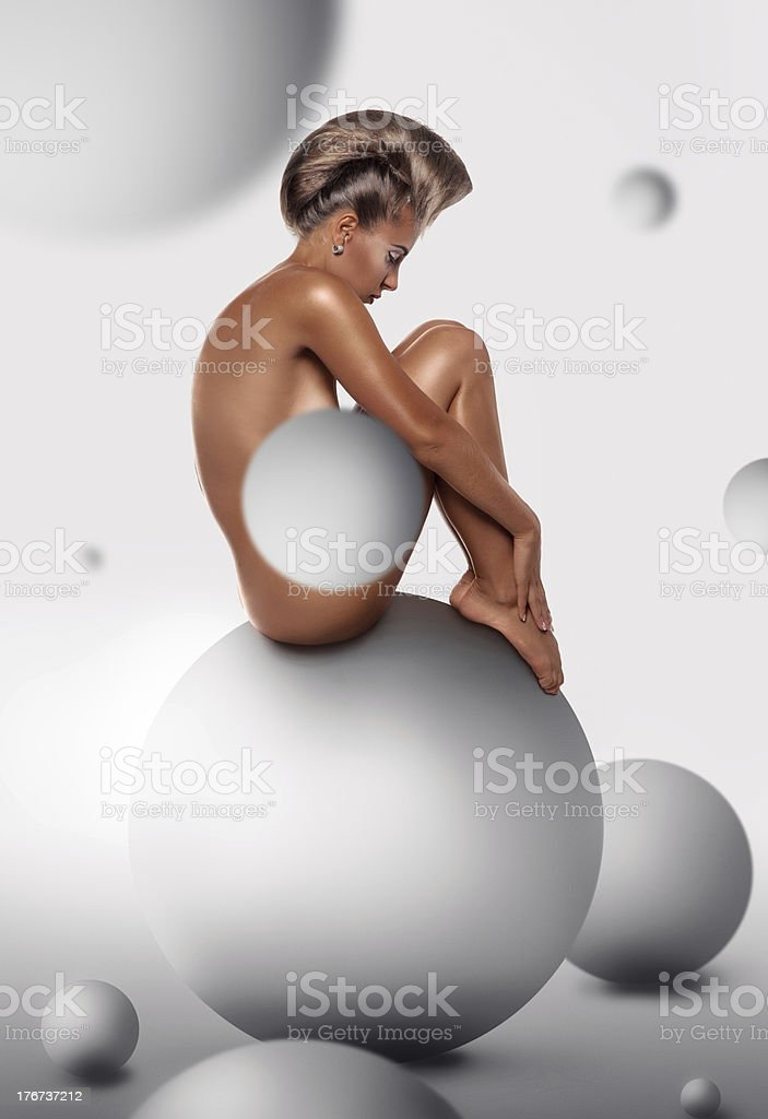 woman with unusuall hairstyle sit on ball in studio royalty-free stock photo