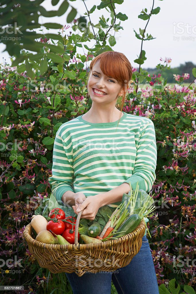 Woman With Vegetable Basket Outdoors stock photo