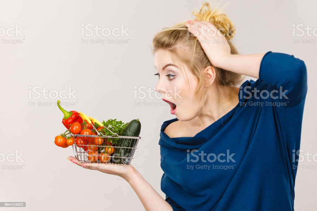Woman with vegetables, shocked face expression stock photo