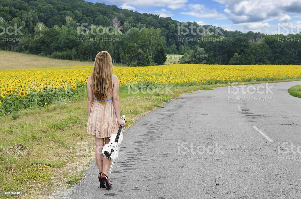Woman with vilolin by country road stock photo