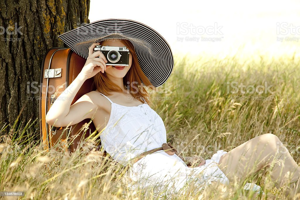 Woman with vintage camera sitting outdoors stock photo