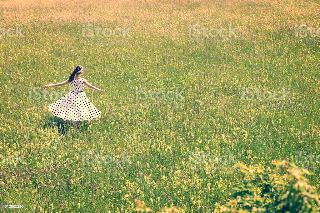 Woman with vintage outfit is dancing on the meadow stock photo
