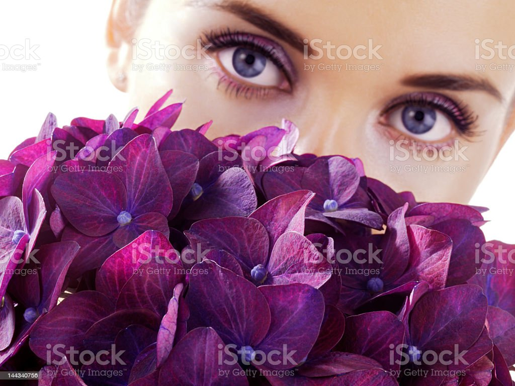 Woman with violet colored eyes looks out from purple flowers royalty-free stock photo