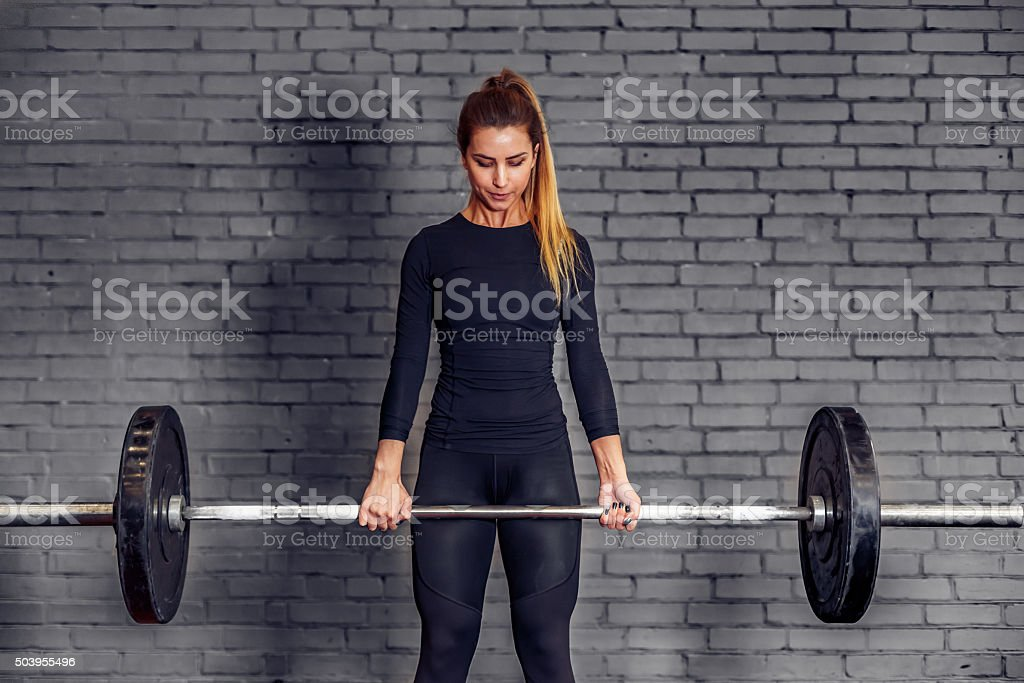 Woman with weight barbell doing deadlift exercise stock photo