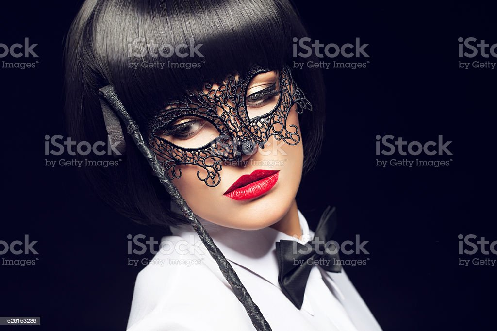 Woman with whip and mask stock photo