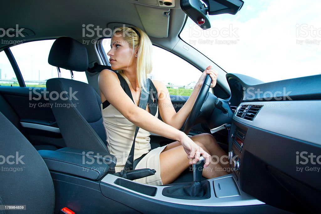 Woman with white skirt looking back while parking car stock photo