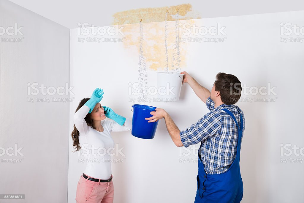 Woman With Worker Collecting Water From Ceiling In Bucket stock photo
