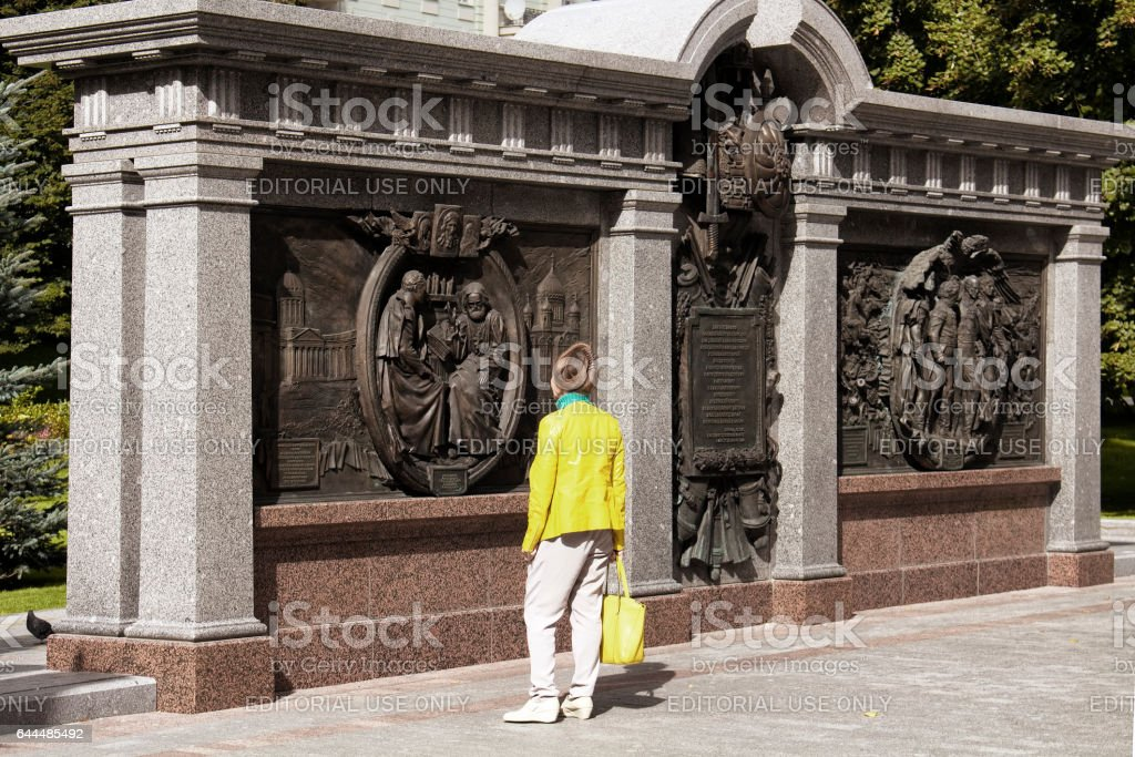 Woman with yellow jacket and bag looks at the monument stock photo