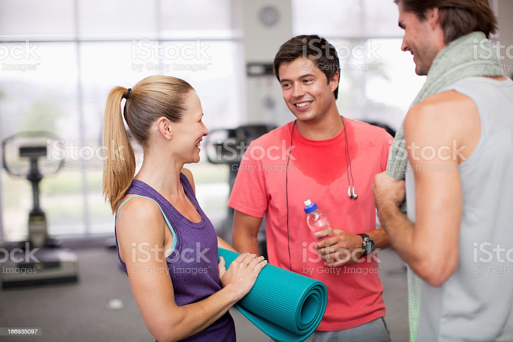 Woman with yoga mat talking to men in gymnasium royalty-free stock photo