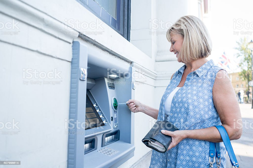 Woman withdrawing cash from an ATM stock photo
