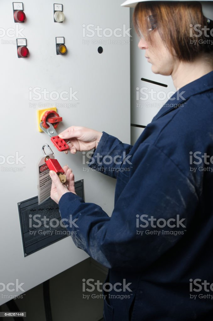 Woman worker locking out electrical box stock photo