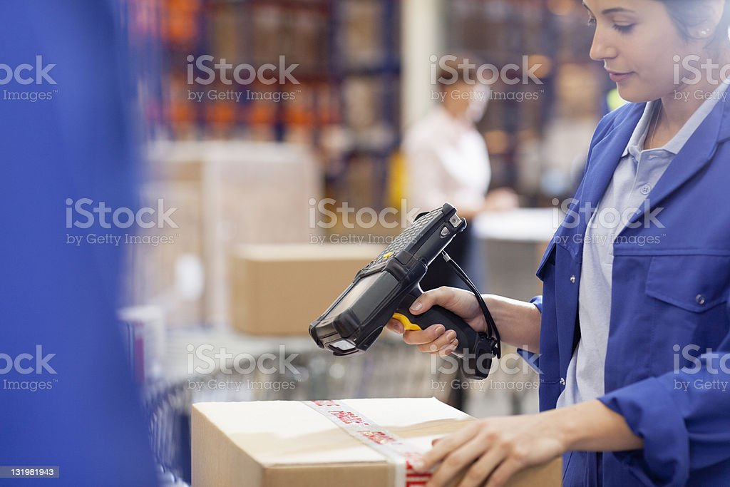 Woman worker scanning cardboard box with bar code reader stock photo