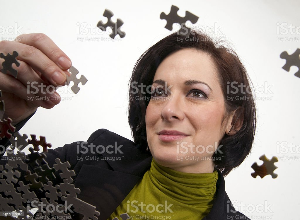 Woman Working a Jigsaw Puzzle Putting Pieces Together royalty-free stock photo
