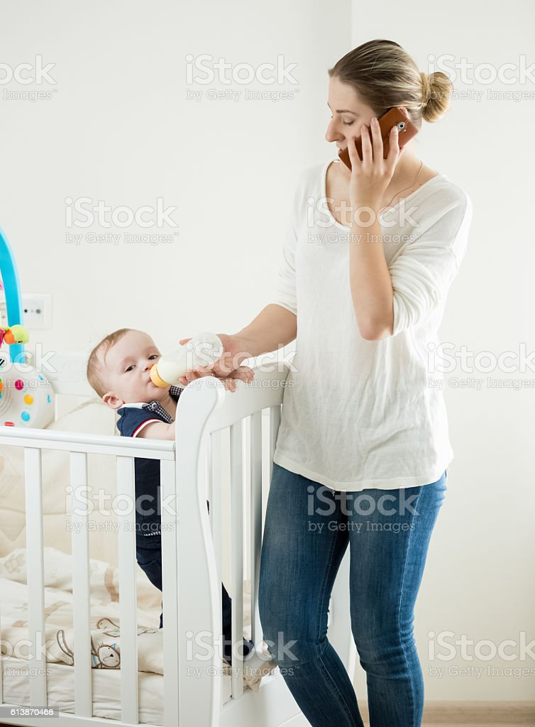 Woman working and talking by phone while feeding baby stock photo