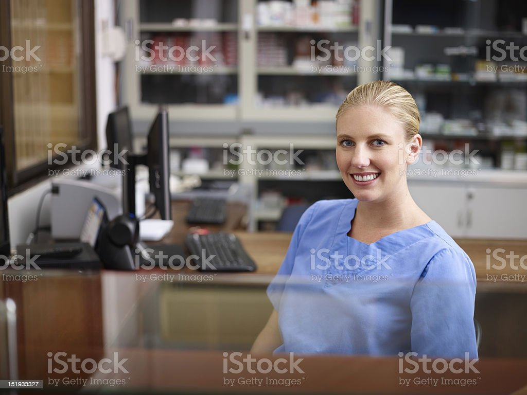 Woman working as nurse at reception desk in clinic stock photo