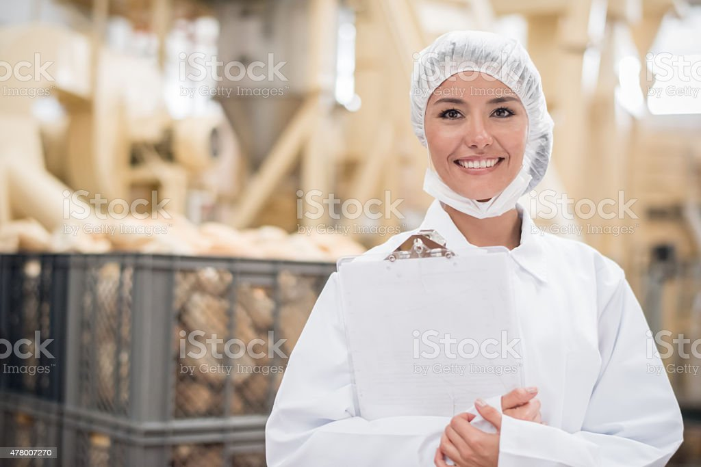 Woman  working at a bread factory stock photo