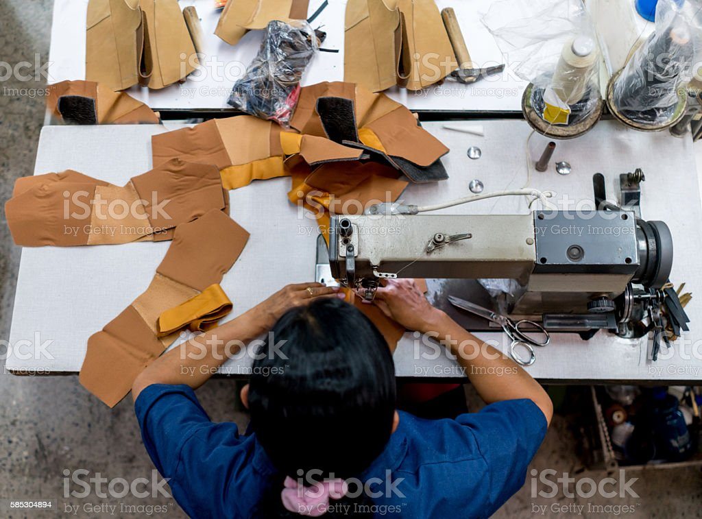 Woman working at a factory making shoes stock photo
