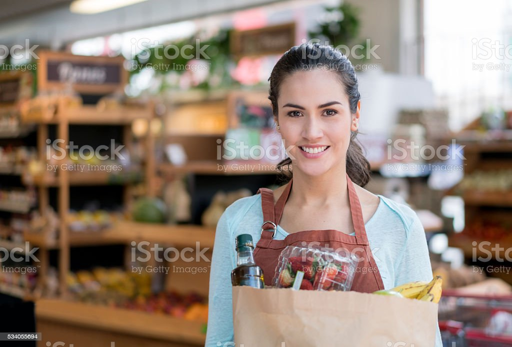 Woman working at a food market holding groceries stock photo