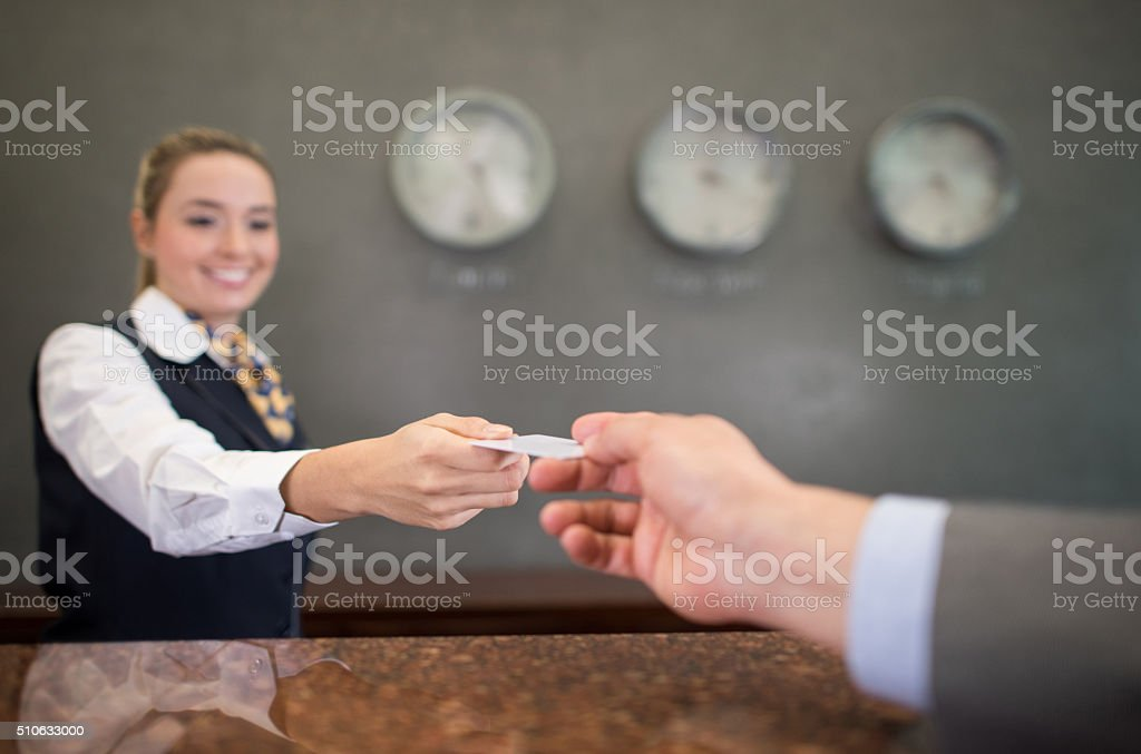 Woman working at a hotel handing a loyalty card stock photo