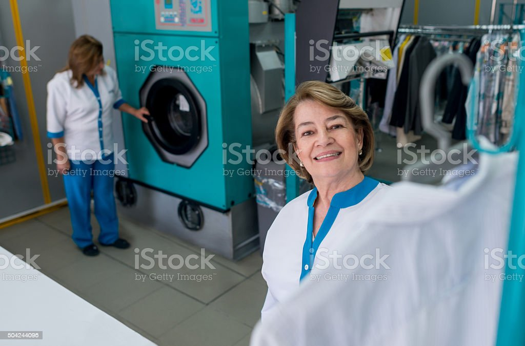 Woman working at a laundry service shop stock photo