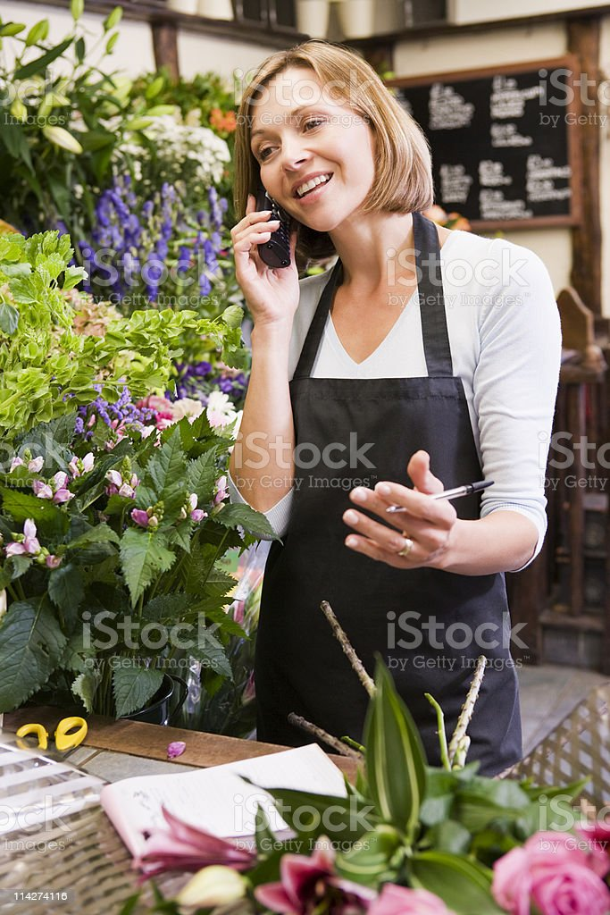Woman working at flower shop using telephone stock photo