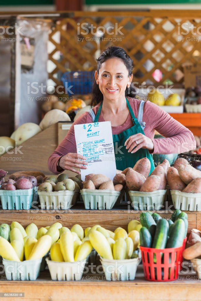 Woman working at fruit and vegetable stand, price sign stock photo